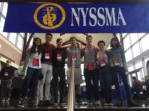 Students stand under NYSSMA banner