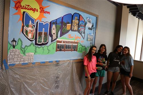 Students stand in front of mural