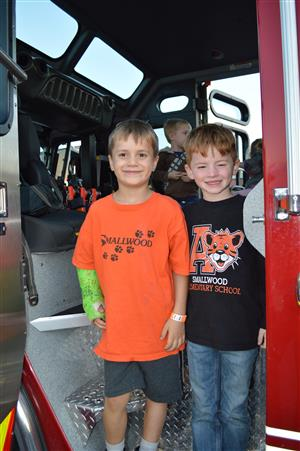 Two boys stand on fire truck