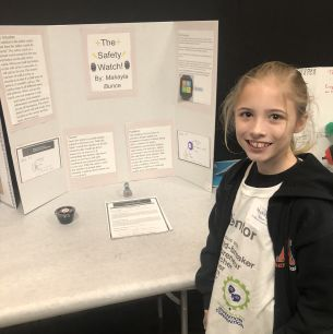 Student stand next to her invention