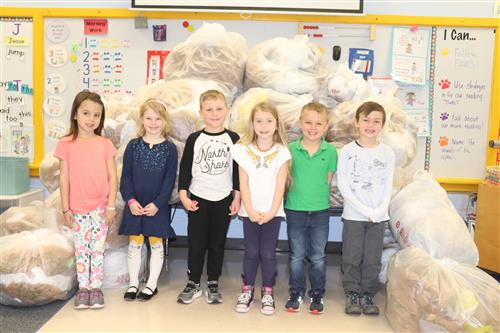 Students stand in front of all the bags collected