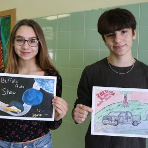 Two students hold posters