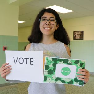 Student holds a vote sign and card design