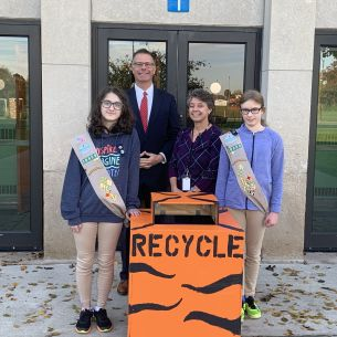 Students stand by recycling bin