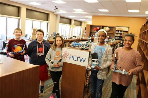 Five middle school students hold their projects