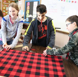students cut fleece blankets