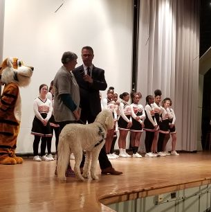 Students and dog on stage