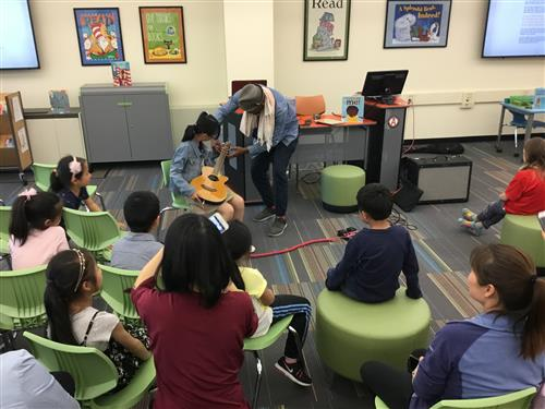 Student plays guitar with Mr. Evans