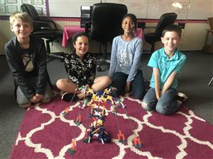 Four students display their ride project