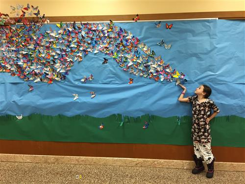 Student stands near butterfly mural