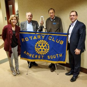 Principal and Rotary members stand near a banner