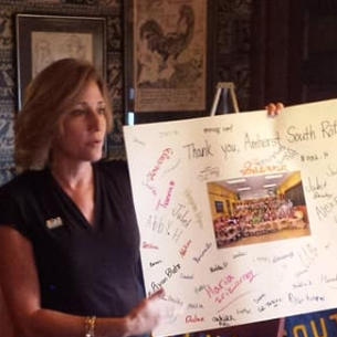 Principal holds sign with thanks for Rotary Club