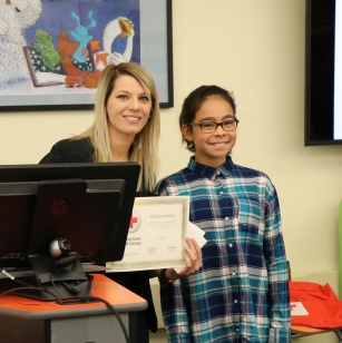 Elementary student receives certificate from Red Cross employee