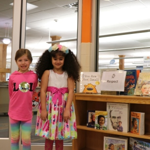 Two girls wearing colorful clothing stand next to a display of books