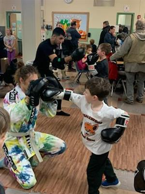 Kid boxing with instructor