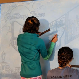 Students trace outline of mural