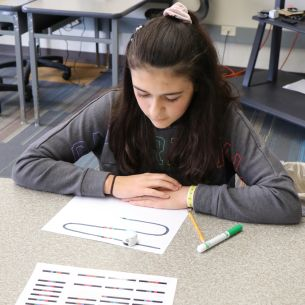 Student watches Ozobot robot follow track