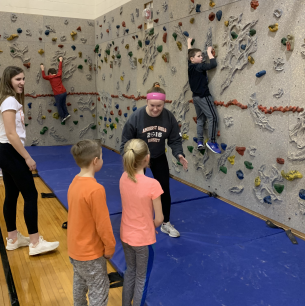 Students climb on rock wall