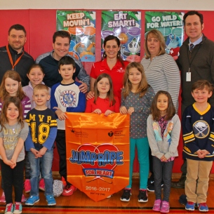 Students and teachers hold banner for heart health jump rope